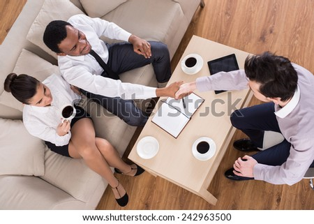 Top view of business people are shaking hands while working in cosy meeting room.