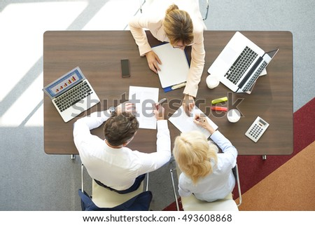 Top view of business people working together at office while using laptops and consult about investment idea.