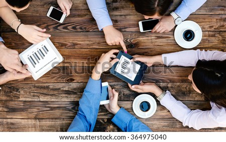 Top View of Business Team Young People Hands holding Electronic Gadgets with Professional Charts discussing and interacting - stock photo