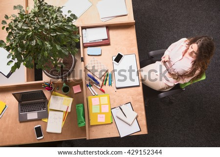Top view of business woman sitting at table and working in office. Beautiful freelance lady in white suit looking in front of her. - stock photo