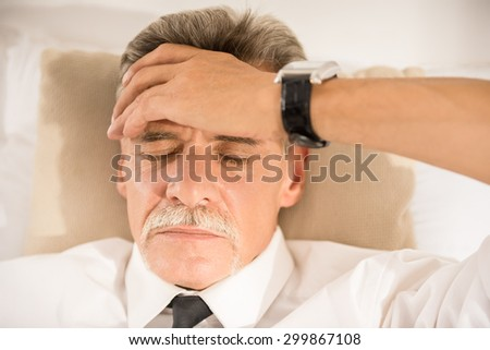 Top view of businessman is sleeping on bed in suit. - stock photo