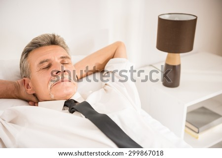 Top view of businessman sleeping on bed at hotel room. - stock photo