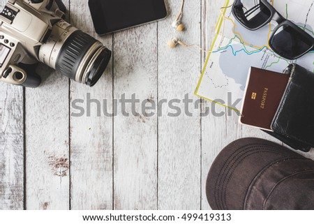 Top view of Camera with cap,sunglasses,wallet,smart phone,map and passport on white wooden table background, Travel concept