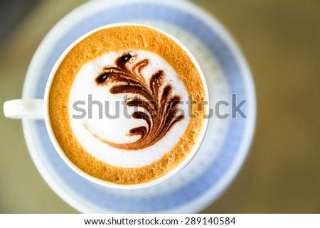 Top view of cappuccino coffee with flower art on foam  - stock photo