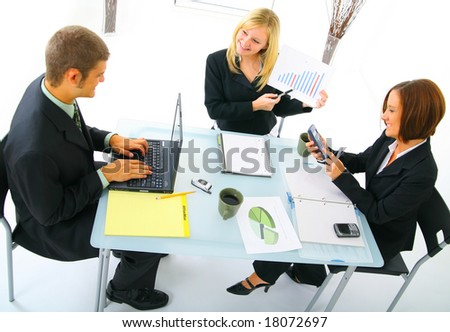 top view of caucasian businesswoman presenting sales figure while two other business people taking note and calculating