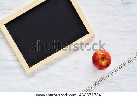 Top view of chalkboard with copyspace, an apple and tape measure. Fitness and diet concept. - stock photo