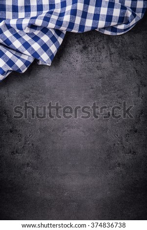 Top view of checkered kitchen tablecloth on granite -  concrete - stone background. Free space for your text or products. - stock photo