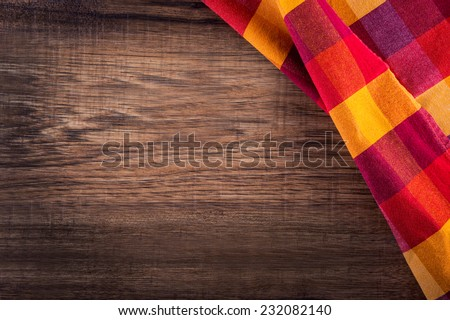 Top view of checkered napkin on empty wooden table  - stock photo