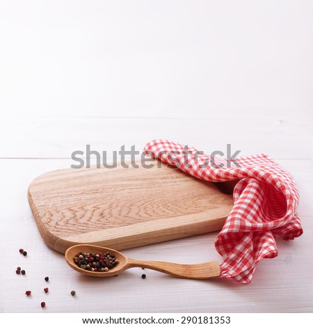 Top view of checkered napkin tablecloth on white wooden table. Empty cutting board. Unique perspectives horizontal