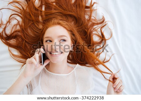 Top view of cheerful playful young woman smiling and talking on cell phone in bed - stock photo