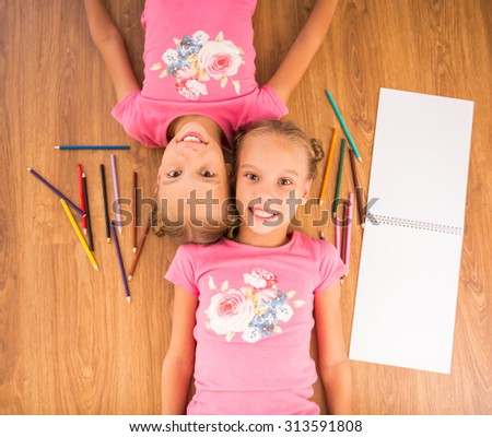 Top view of cheerful sisters are lying on the floor, with paper and colored pencils. - stock photo