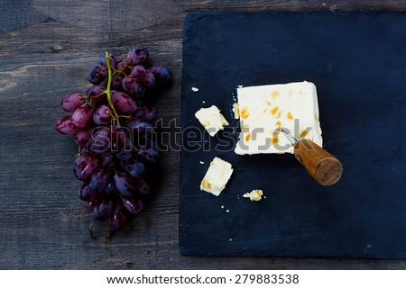 Top view of cheese and grape on dark wooden background. Food concept. - stock photo