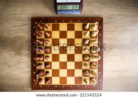 top view of  chessboard with chess and clock - stock photo