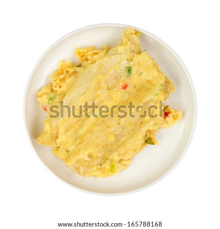 Top view of chicken enchiladas covered in a cheese sauce with rice and vegetables on a white background. - stock photo