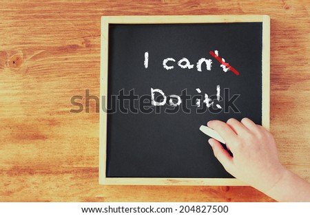 "top view of child hand writing ""i can di it"" over blackboard - stock photo"
