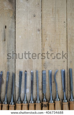 Top view of chisel tools set on wooden surface, closeup flat lay photo - stock photo