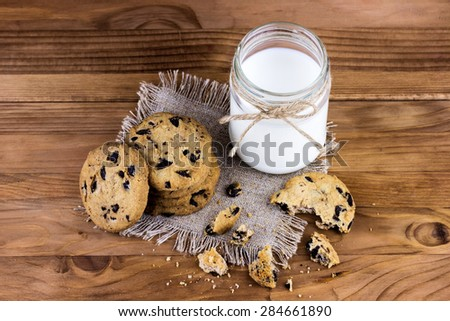 Top view of chocolate chip cookies with small bottle of milk on wooden background - stock photo