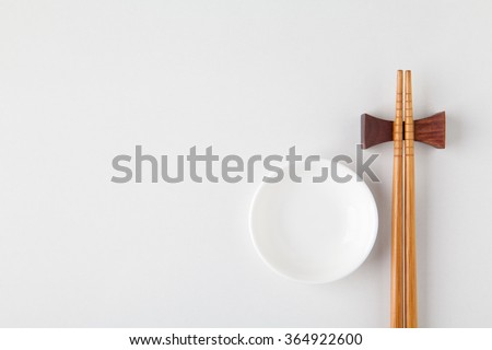 Top view of chopsticks with bowl on white background. - stock photo