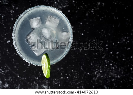 Top view of classic mexican margarita cocktail on black background. Margarita glass full of ice, salt and lime on side. Black background with whites sea salt spots.