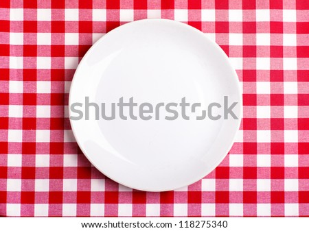 Top view of clean white plate on a tablecloth - stock photo