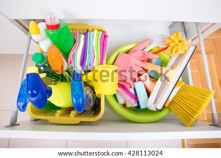 Top view of cleaning supplies and equipment stored in drawer in kitchen cabinet - stock photo
