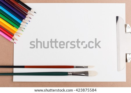 Top view of clipboard with blank paper, colorful pencils and paintbrushes. Mock up - stock photo