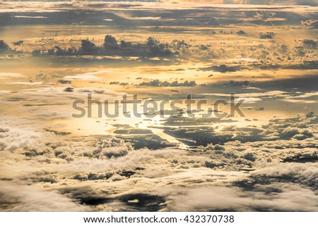 Top view of coast , sea  and raining cloudy with reflex sunset. Captured on airplane. Above the cloud. - stock photo