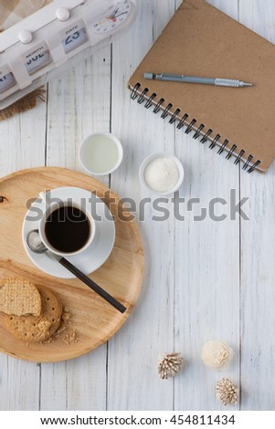Top view of coffee,bread and notepad on white wooden