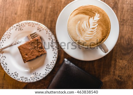 TOP VIEW OF COFFEE, BROWNIE AND PURSE ON WOODEN TABLE (focus at coffee)