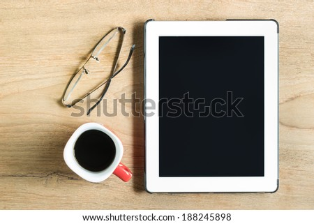 Top view of coffee cup , glasses and tablet on wooden table with space
