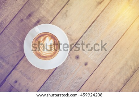 Top view of coffee cup on wooden table with vintage filter