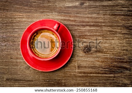 Top view of coffee in red cup on wooden vintage table - stock photo
