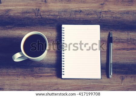 Top view of coffee, notepad and pen on a wooden table, retro style