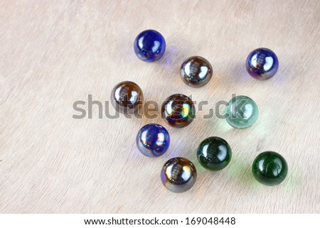 top view of collection of  shiny marbles on wooden background - stock photo