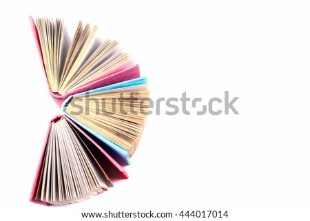 Top view of colorful hardback books in a circle. Open book, fanned pages isolated on white background, free copy space. Back to school copy space. Education background.
