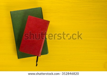 Top view of colorful hardback books on yellow background. Composition with vintage old hardback books, diary, fanned pages on wooden deck table. Books stacking. Back to school. Education background. - stock photo