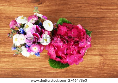 Top view of colorful spring flowers on wooden background