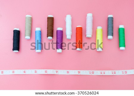 Top view of colorful thread spools and measuring tape on pink background - stock photo
