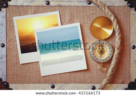 top view of compass, vacation photos and a traveler rope on burlap canvas fabric background with metal frame. explorer and adventure concept. vintage filtered image