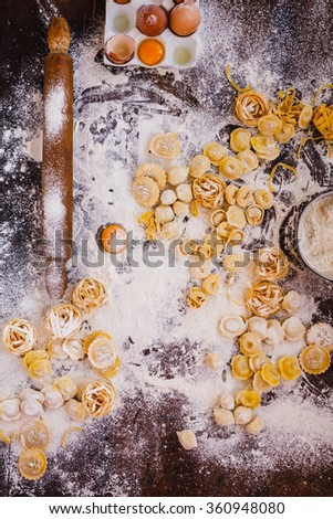 Top view of composition of fresh homemade pasta ravioli, perle, gnocchi, dumplings fettuccine, tortellini over flourish wooden table with rolling pin and fresh egg ready for cooking. Rustic style.  - stock photo