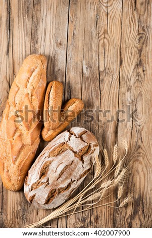 Top view of composition with bread and ears of wheat on wooden background with space.