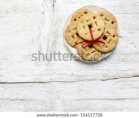 Top view of cookies with red bow on white wooden table. - stock photo