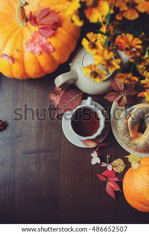 top view of cozy autumn breakfast on table in country house. Hot tea, pumpkins, bagels and flowers.