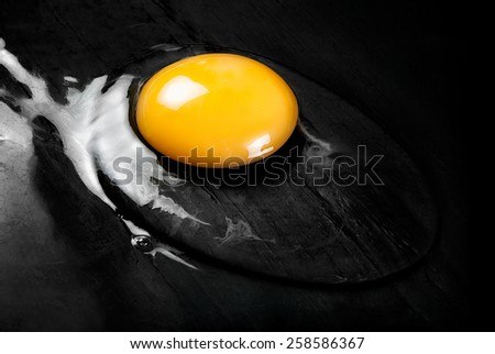 Top View of Cracked Raw Egg with Bright Yellow Yolk on Smooth Black Surface Such as Frying Pan or Counter