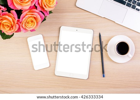 Top view of creative woman's desktop with roses, blank white smart phone and tablet screens, coffee cup, pencil and laptop keyboard. Mock up - stock photo