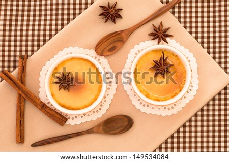 Top view of creme brulee desserts with raw cinnamon and star aniseed. - stock photo