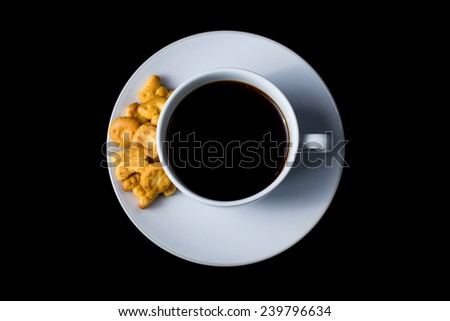Top view of cup of black coffee with alphabet cracker on the side on black background - stock photo
