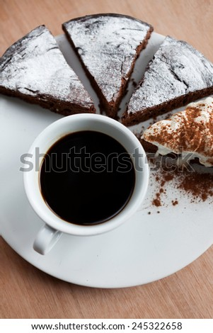 Top view of cup of black coffee with chocolate cake on the white plate - stock photo