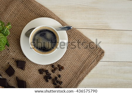 Top view of cup of hot fragrant coffee and coffee beans with chocolate on a mesh fabric. Coffee house. Uplifting mood. Coffee break. Relax. Increasing productivity in the mornings. Coffee breakfast. - stock photo