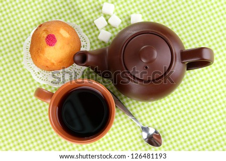 Top view of cup of tea and teapot on green tablecloths